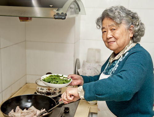 Older lady cooking food in a wok