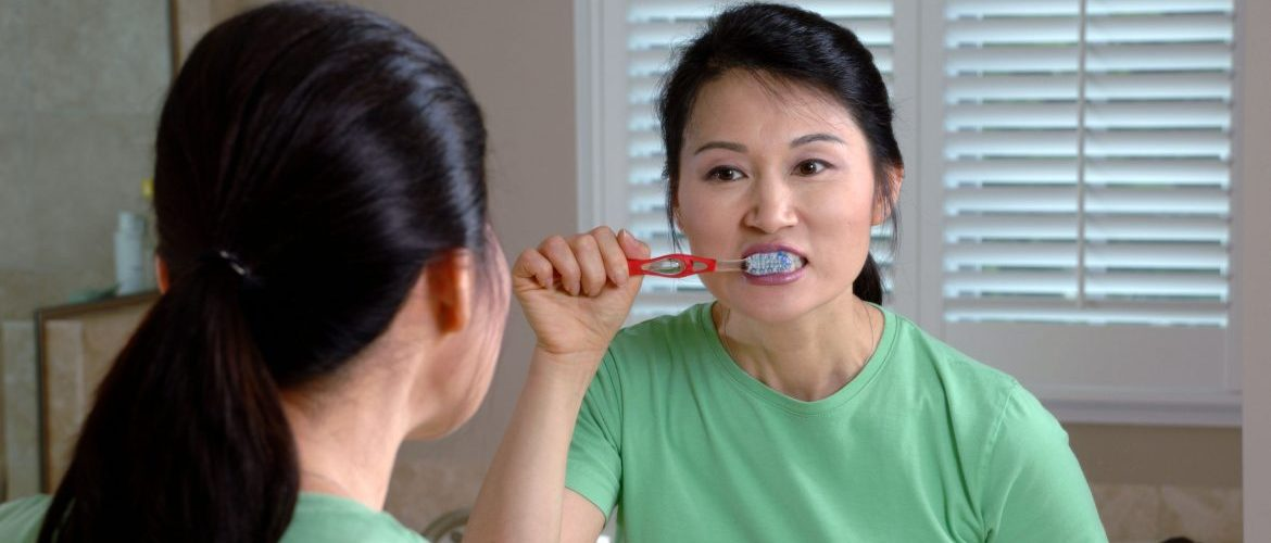 17067-an-asian-woman-brushing-her-teeth-in-a-mirror-or
